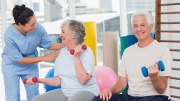 Happy trainer communicating with senior woman sitting by man in gym
